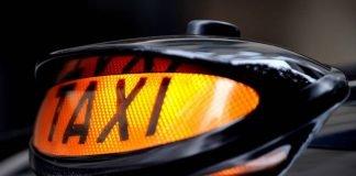 Illuminated taxi sign on a black cab